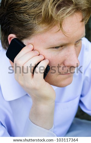 Young Business Man Holds Smart Phone to His Ear