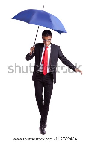 young business man in an equilibrium act, helped by an umbrella, walikng forward