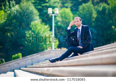 Young business man in dark suit on stairs