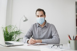 Young business man in gray shirt sterile face mask sitting at desk work on laptop pc computer in light office on white wall background. Achievement business career concept. Writing notes in notebook