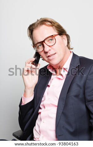 Young business man in office calling with cellphone wearing blue suit, pink shirt and glasses.