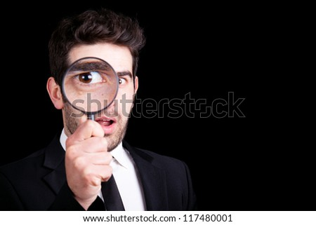 Young business man in suit looking to magnifying glass