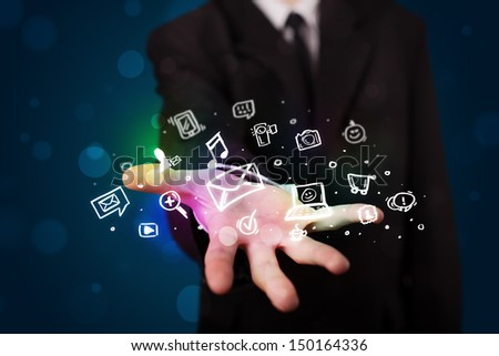 Young business man in suit presenting colorful glowing social media icons