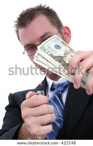 Young business man in suit, tie, glasses, burning twenty dollar bills.