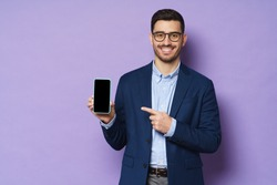 Young business man in suit, wearing eyeglasses, holding blank screen smartphone and pointing to it, copy space for advertising, isolated on purple background