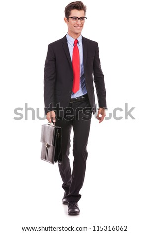 young business man is walking an looking away from the camera while holding a suitcase