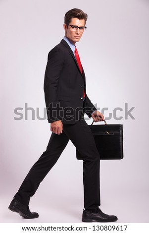 young business man is walking and looking at the camera while holding a suitcase . gray background