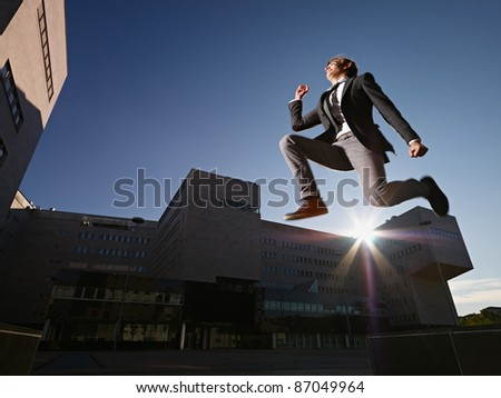 young business man jumping for joy outdoors, with office buildings and sun in background. Horizontal shape, side view, copy space