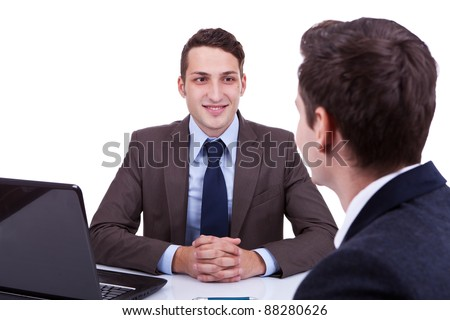 young business man listening at his desk to his employee, over white