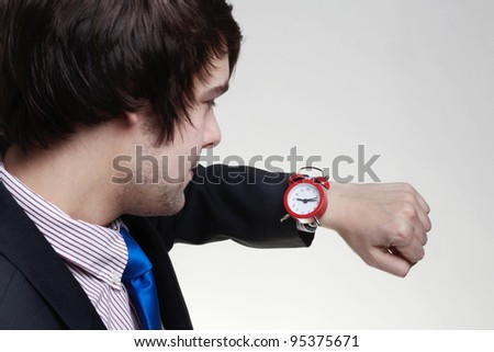 young business man looking at a large watch on his wrist
