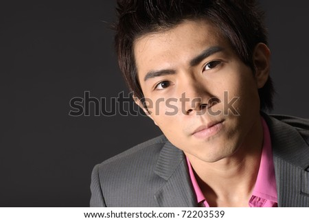 Young business man of Asian, closeup portrait on dark background.
