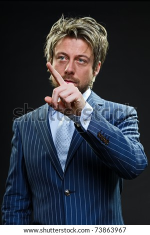 Young business man pointing with finger wearing sunglasses in blue striped suit. Explaining. Touching. Screen. Short blond hair. Studio portrait. Black background.