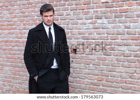 young business man posing against a brick wall with his hands in his pockets while looking into the camera