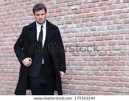 young business man posing outdoor with a strong expression while looking into the camera