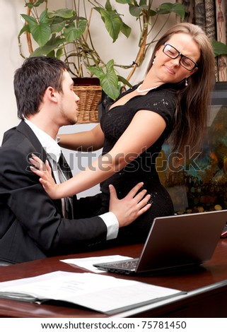 Young business man sexually harassing woman in office