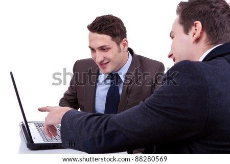 young business man showing something to his partner on the screen of his laptop - stock photo