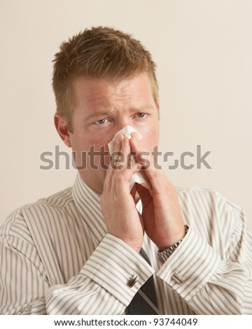 Young business man sick blowing nose on tissue