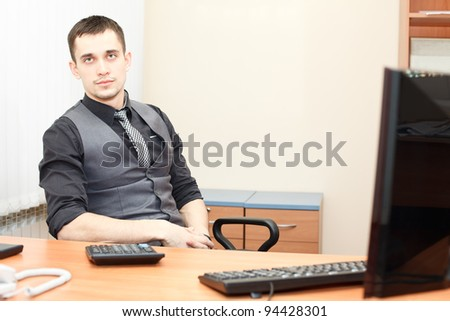 Young business man sitting at table and working on computer
