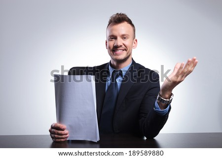 young business man sitting at the office and welcoming you with some papers in a hand and a smile on his face. on a light gray studio backgroud