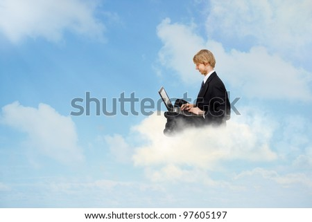 Young business man sitting on clouds and using a laptop - stock photo