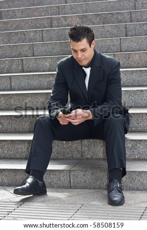 young business man sitting on steps sending a message.