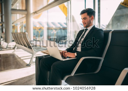 Young business man sitting on the computer with the suitcase at the airport waiting for the flight  #1024056928