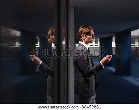 young business man standing out of office building and reading emails on mobile phone. Horizontal shape, waist up, copy space