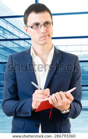 Young business man taking notes for the next meeting looking confused over big office\'s windows background