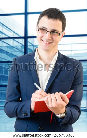 Young business man taking notes for the next meeting looking happy over big office\'s windows background