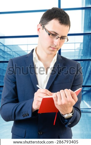 Young business man taking notes for the next meeting over big office\'s windows background