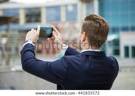 Young business man taking pictures on a mobile phone, summer street outdoors