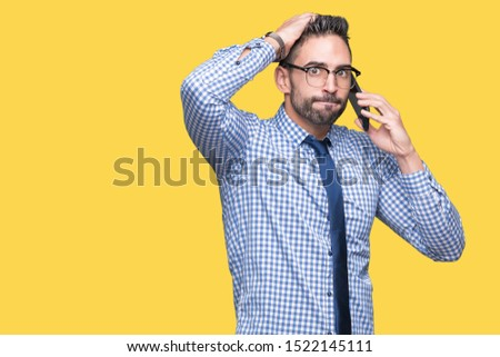 Young business man talking on the phone over isolated background stressed with hand on head, shocked with shame and surprise face, angry and frustrated. Fear and upset for mistake.
