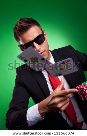 Young business man throwing a pair of aces. On green background