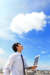 Young business man using laptop and look to blue sky and cloud with cityscape in the background, business and cloud computing concept