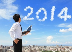 Young business man using laptop and look to 2014 year text with blue sky and cloud and cityscape in the background, business and cloud computing concept