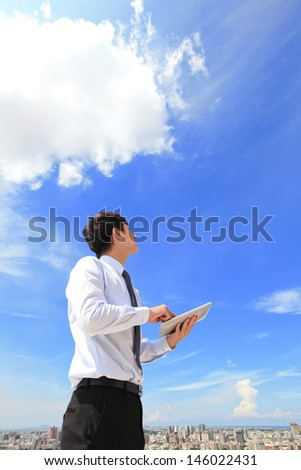 Young business man using tablet pc and look to blue sky and cloud with cityscape in the background, business and cloud computing concept