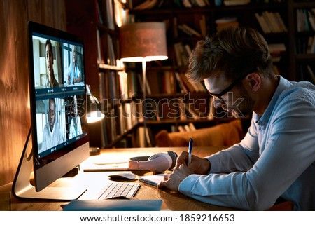 Young business man video conference calling using computer social distance working from home office. Remote male professional videoconferencing by virtual team online web meeting group chat.