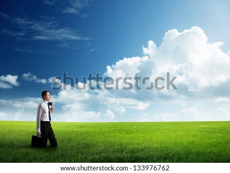 young business man walking at the field of grass