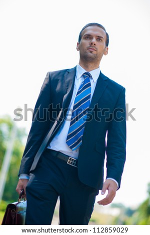 young business man walking in the park