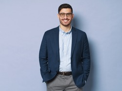 Young business man wearing formal clothes and eyeglasses, standing isolated against blue background in relaxed pose, smiling friendly