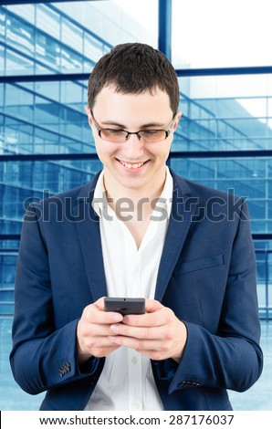 Young business man wearing glasses and texting a massage on his smartphone over big office\'s windows background