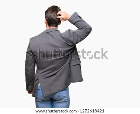 Young business man wearing glasses over isolated background Backwards thinking about doubt with hand on head