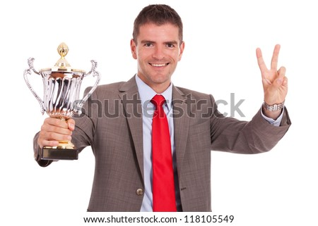 young business man winning a big trophy and making victory hand gesture