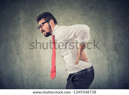 young business man with backache on gray background