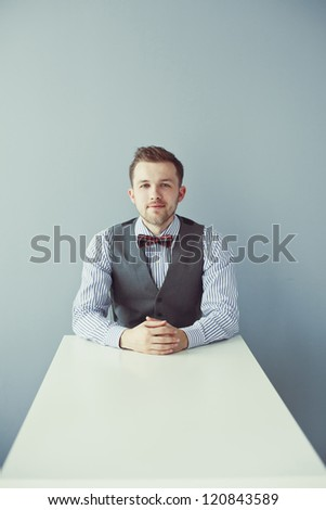 Young business man with bowtie and jacket sitting at the table