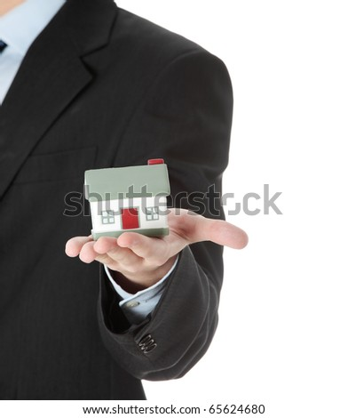 Young business man with house model on hand- real estate concept. Isolated on white