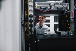 Young business man with laptop working in data center