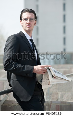 Young business man with newspaper. - stock photo