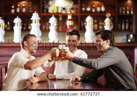 Young business men in a bar with beer