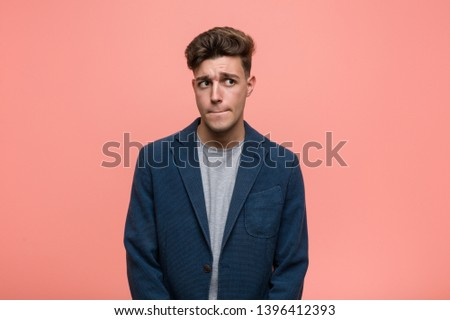 Young business natural man confused, feels doubtful and unsure.